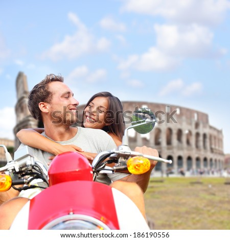 Rome couple on scooter by Colosseum Italy Romantic happy lovers driving scooter on honeymoon having fun in front of Coliseum Love and travel concept with multiracial couple