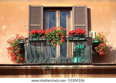 Rome, Italy. Beautiful window decorated with red flowers.