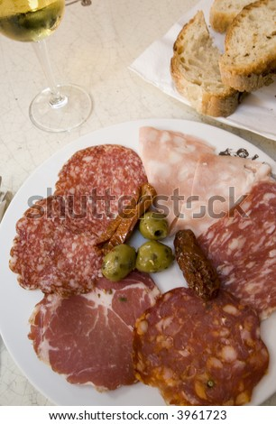 rome italy ham prosciutto salami plate with white wine and crusty italian bread - stock photo