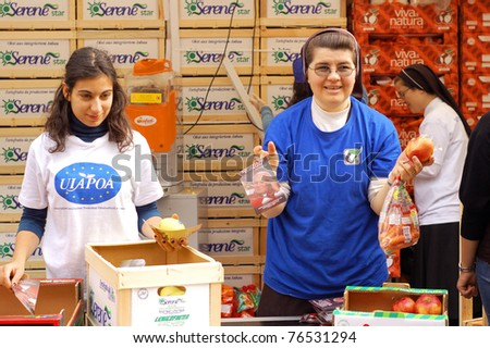 ROME, ITALY - MAY 1: Female volunteers hand out snacks to people attending the beatification of Pope John Paul II in Rome, Italy on May 1, 2011.