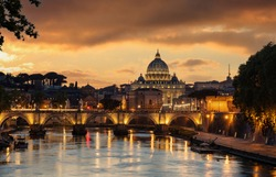 Rome Italy. Saint Peter Basilica in the Vatican over illuminated Sant Angelo bridge and Tiber river night view, orange color sky after sunset