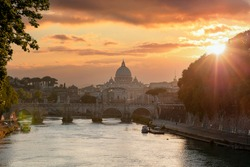Rome Italy. Saint Peter Basilica in the Vatican over Sant Angelo bridge and Tiber river, cloudy sky at sunset background