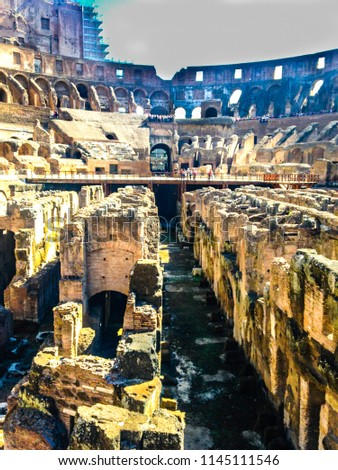 ROME, ITALY - 27.09.2015: Tourists visiting the interior of the Colosseum, one of the New Seven Wonders of the World. Inside view of ancient amphitheatre of Colosseum built by Vespasian and Titus.