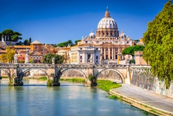 Rome, Italy. Vatican dome of Saint Peter Basilica (Italian: San Pietro) and Sant'Angelo Bridge, over Tiber river.