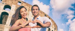 Rome romantic travel destination happy couple in love making heart shape hands showing romance getaway for honeymoon holiday panoramic banner.