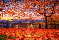 Rome, Vatican - autumn park bench with red leaves and St Peter's basilica and Rome in the background at sunset