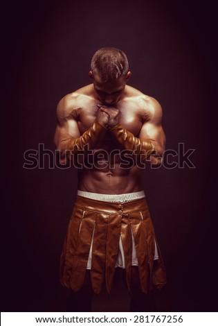 Rome warrior praying on the black background