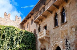 Romeo and Juliet balcony. Courtyard of Casa di Giulietta (House of Juliet or House of Cappelletti) against with Jet plane, Airliner in high flight with vapor trail. Travel destination Verona, Italy