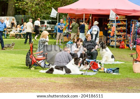 RONNEBY, SWEDEN - JULY 05, 2014: Blekinge Kennelklubb international dog show. People sitting with dogs on blankets on the ground.
