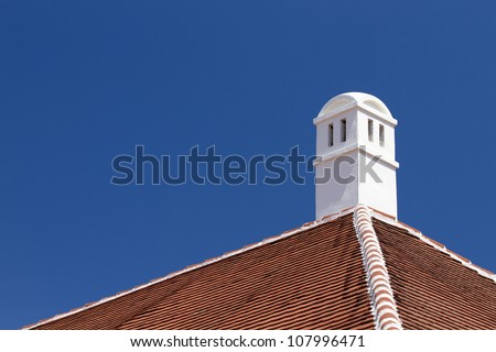 Roof and chimney with clear blue sky.