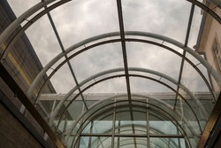 Roof architecture with curved glass for a passageway