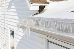 Roof gutter full of ice and icicles after winter storm. Concept of roof damage, home maintenance and repair.