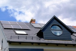 roof installed photovoltaic PV sun collector solar panels. blue sky. sloped gray metal residential roof in daylight. alternative and clean energy generation. self sufficiency and off grid concept.