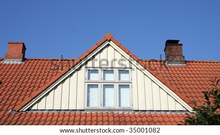 roof loft conversion or dormer. tiled house with chimneys and windows against blue sky