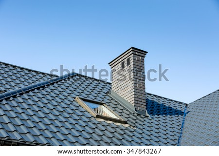 Roof of a detached house with a skylight and chimney against the sky #347843267