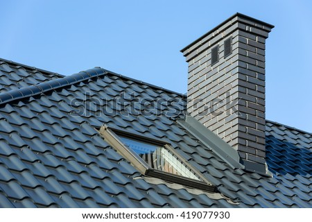 Roof of a detached house with a skylight and chimney against the sky #419077930
