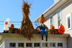 Roof of a house decorated for Halloween with corn, pumpkins, scarecrows and a ghost