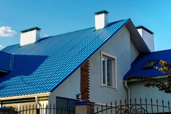Roof of a house or cottage made of blue metal tiles with drains, slopes, tides, chimney against the blue sky. Metal roof for roof design, construction, architecture.