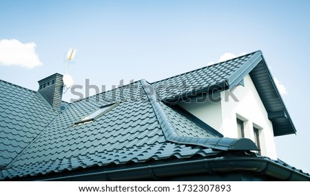 Roof of a new home. Ceramic chimney, metal roof tiles, gutters, roof window. TV antennas attached to the chimney. Single family house.
