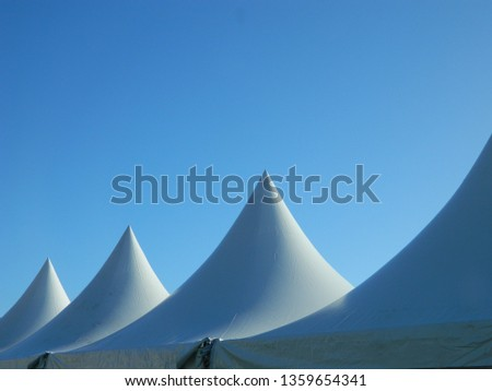 Roof of a number of marquees/tents on blue sky background #1359654341