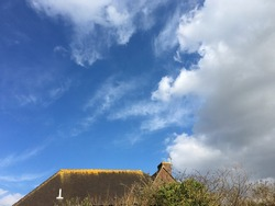 Roof of an old house with yellow lichens along the edge against blue sky and white clouds with space for runaround or wraparound text