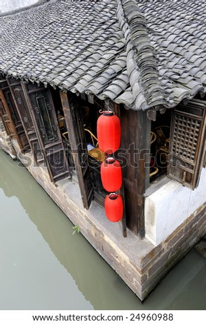 Roof of an old traditional tea house with red Chinese lantern in the water town of Wuzhen near Shanghai in China