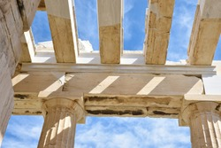 Roof structure and ceiling of Propylaea, monumental gateway to world heritage Acropolis shown doric columns and architrave built with marble and limestone on blue sky background, Athens, Greece