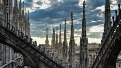 Roof terraces of gothic Milan Cathedral, or Duomo di Milano, at sunset. The beautiful gothic cathedral is the main tourist attraction of Milan, Lombardy, Italy