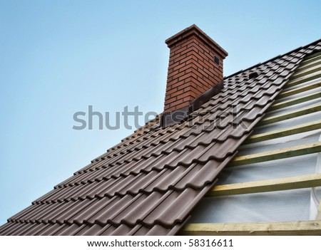 Roof under constructions with lots of tile and red brick chimney