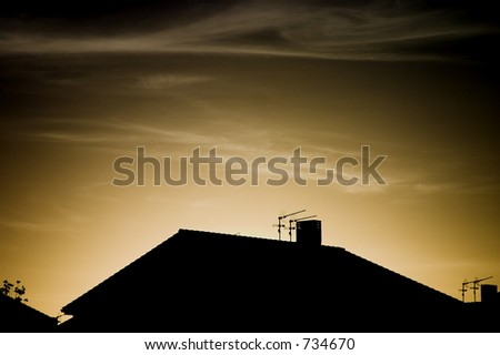 Roof with antennas at the sunset.