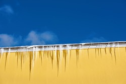 Roof with big melting icicles, risk of injury. Sharp icicles hanging down from roof of building against sunny background. Transparent icicle on facade of building