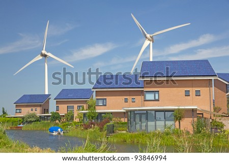 Roof with solar panels and wind turbines in the background