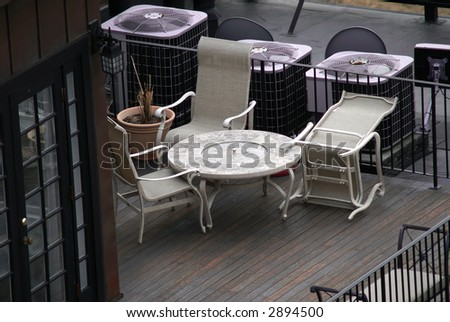 roofdeck with chairs, one is overturned, french doors on left,air handlers behind chairs