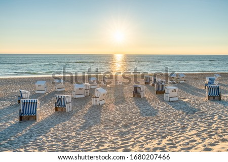 Roofed wicker beach chairs at the North Sea coast on Sylt, Germany