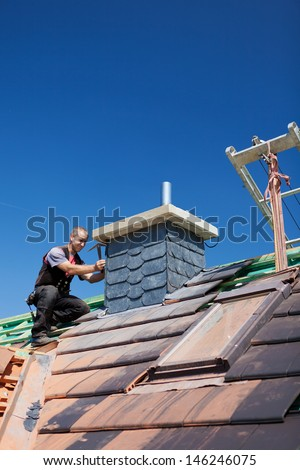 Roofer assembling tiles on a chimney of an unfinished roof