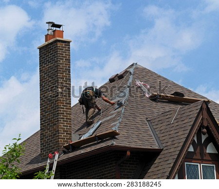 roofer at work repairing a steeply sloped shingle roof