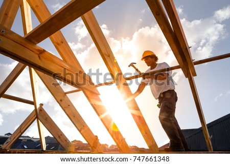 roofer,carpenter working on roof structure on construction site