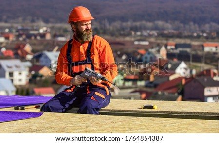 Roofer constructing roof. Man roofing surface. Materials requirements. Install partially overlapping layers of material over roof insulation surfaces. Master repair roof. Flat roof installation.