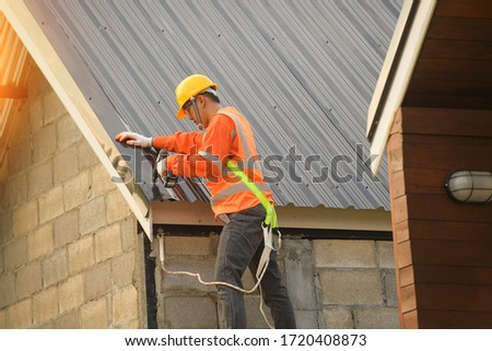 Roofer Construction worker install new roof,Roofing tools,Electric drill used on new roofs with Metal Sheet.
