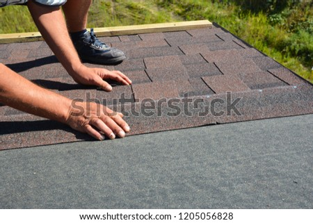 Roofer hands laying Asphalt Shingles on house construction roof. Roofing construction with Asphalt Shingles.