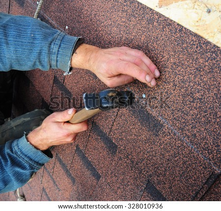 Roofer Install Bitumen Roof  Asphalt Shingles with Hammer - Closeup on Hands. Roofing Repair