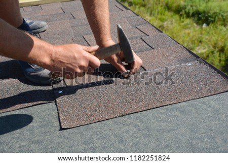 Roofer installing Asphalt Shingles  on house construction roof corner with hammer and nails. Roofing construction with Asphalt Shingles.