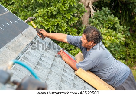 Roofer installing shingles on roof