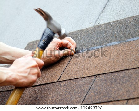 roofer made a roof with slates hammer in hand