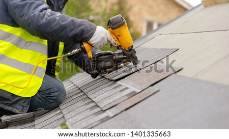 Roofer worker in special protective work wear and gloves, using air or pneumatic nail gun and installing asphalt or bitumen shingle on top of the new roof under construction residential building