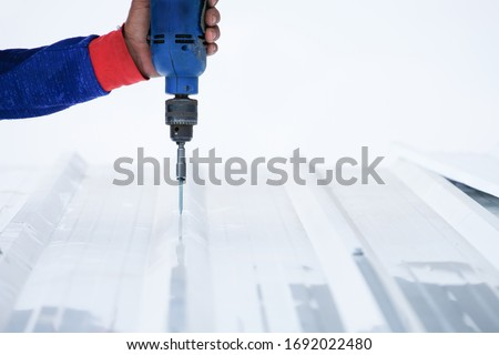 Roofer worker install new metal Sheet roof, Electric drill used on new roofs with Metal Sheet, construction worker install new roof,Roofing tools, Installing screw for roof by Electric drill.