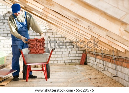 Roofer worker loading red clay tiling into wheel barrow for distribution