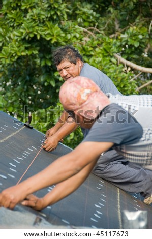 Roofers installing shingles on roof using chalk lines for correct installation