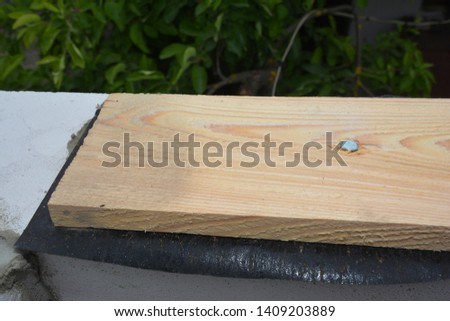 Roofing construction house with wooden beams, rafters, trusses, timber foundation and bitumen waterproofing membrane. Close up on metal anchor bolt roof beam for connection #1409203889