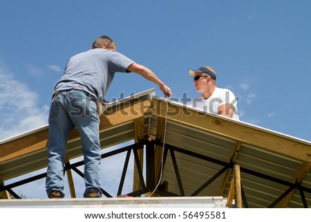Roofing construction workers apply sheet metal to a barn roof.